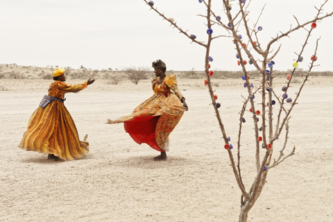 In an arid landscape with dusty earth, two women dressed in bright orange, flowing dresses dance, their clothes swaying with movement. To the right of the image stands a thorny tree with no foliage which has been decorated with small, brightly coloured balls.