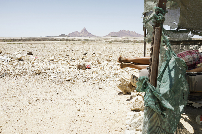 An arid landscape with mountains along the horizon line in the distance. To the right in the foreground, there is a woman laying down in a man-made shelter. Her legs stick out of the shelter and we see her bare feet.