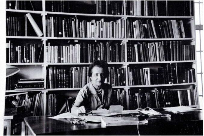 Black and white photograph of Lou Landauer sitting infront of bookshelves atthe Leo Baeck Institute, New York