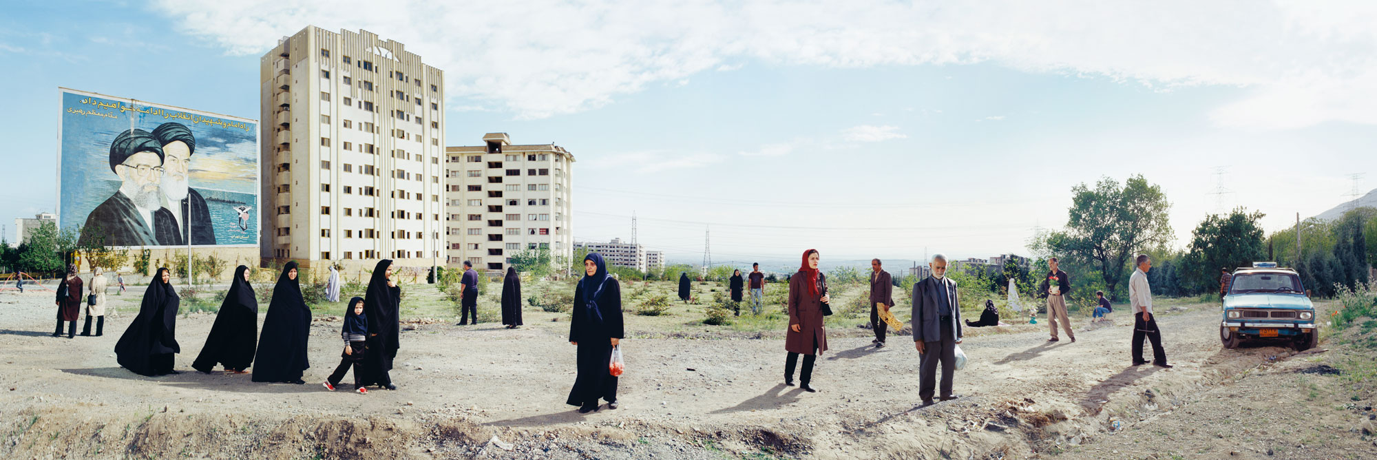 A panoramic view of the outskirts of a city. A number of muslim women and men are dispersed across the scene, either walking or standing. In the background we see a large billboard next to two apartment blocks.