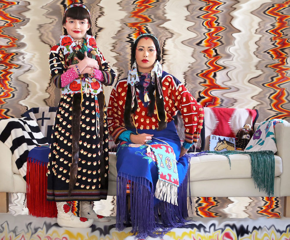Self-portrait of artist Wendy Red Star, seated on a sofa with a young girl standing to her right. Both wear colourful Native American clothing, and the sofa is also covered with bold cloths .