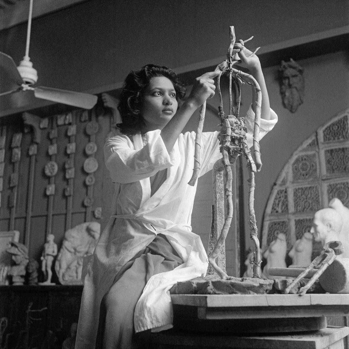 Rehana Mogul at the Sir JJ School of the Arts, Bombay, Early 1940s, Homai Vyarawalla. A woman is seen in a white artist coat building a sculpture