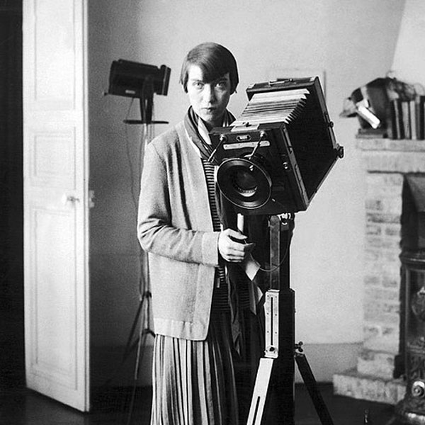 Black and white portrait of photographer Berenice Abbott standing next to a large camera. Flâneur