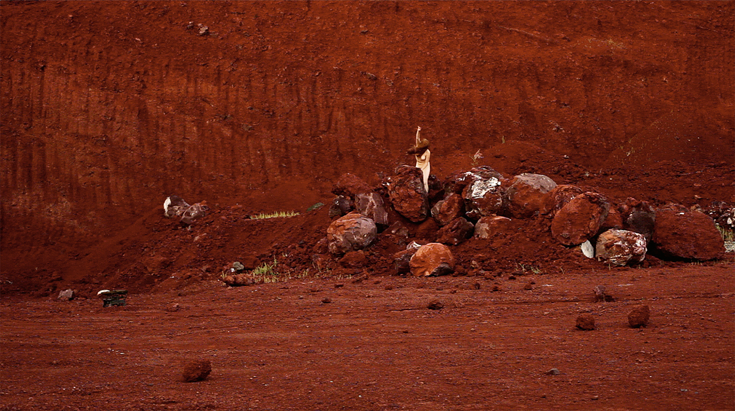 Stories No Longer Untold: Fall, 2013, From the series Four Ages of Woman. Still image. Video by Fatma Bucak. A naked white woman is seen in the distance against a red dry, sandy terrain with large red boulders, she has long ginger hair and is holding an arm up.
