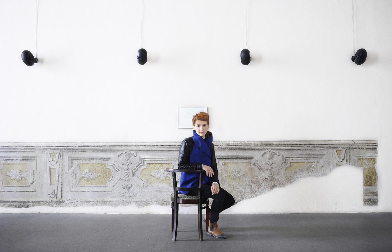 Stories No Longer Untold: Portrait of artist Fatma Bucak by Castello di Rivoli. The photographer it's sideways on a chair wearing a blue scarf