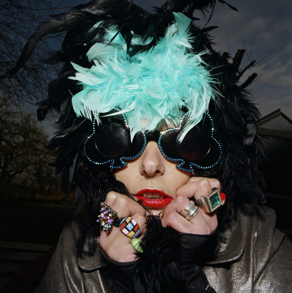 From the exhibition of A Picture of Health, a woman with big jazzy sunglasses is clunching a black and blue feather boa around her head, she's wearing large novelty rings.