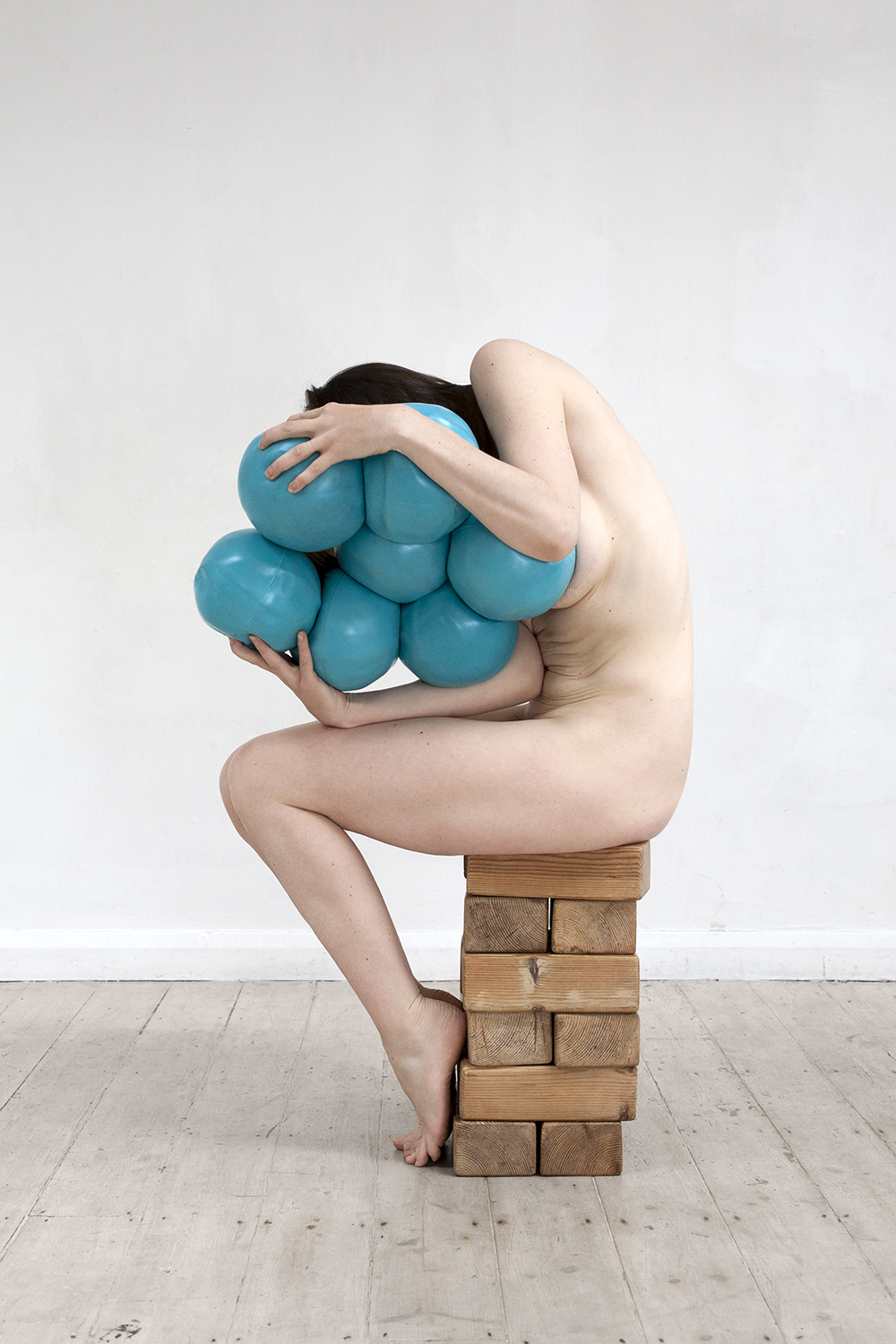 From the A Picture of Health exhibition, a naked woman clutches large squishy blue balls as she's sat on a stack of bricks hunched over