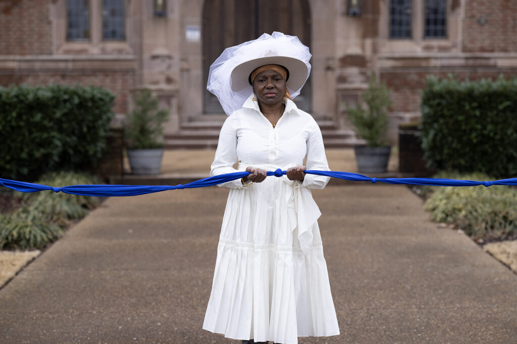 Creator of When We Gather, photographer María Magdalena Campos-Pons standing dressed in white with white hat holding a knotted blue fabric.