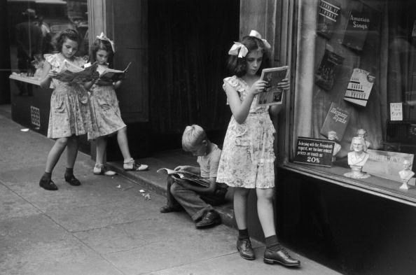 1947: EXCLUSIVE Four children, three girls and one boy, loiter on a sidewalk by a store display window while reading comic books, New York City. (Photo by Ruth Orkin/Hulton Archive/Getty Images)