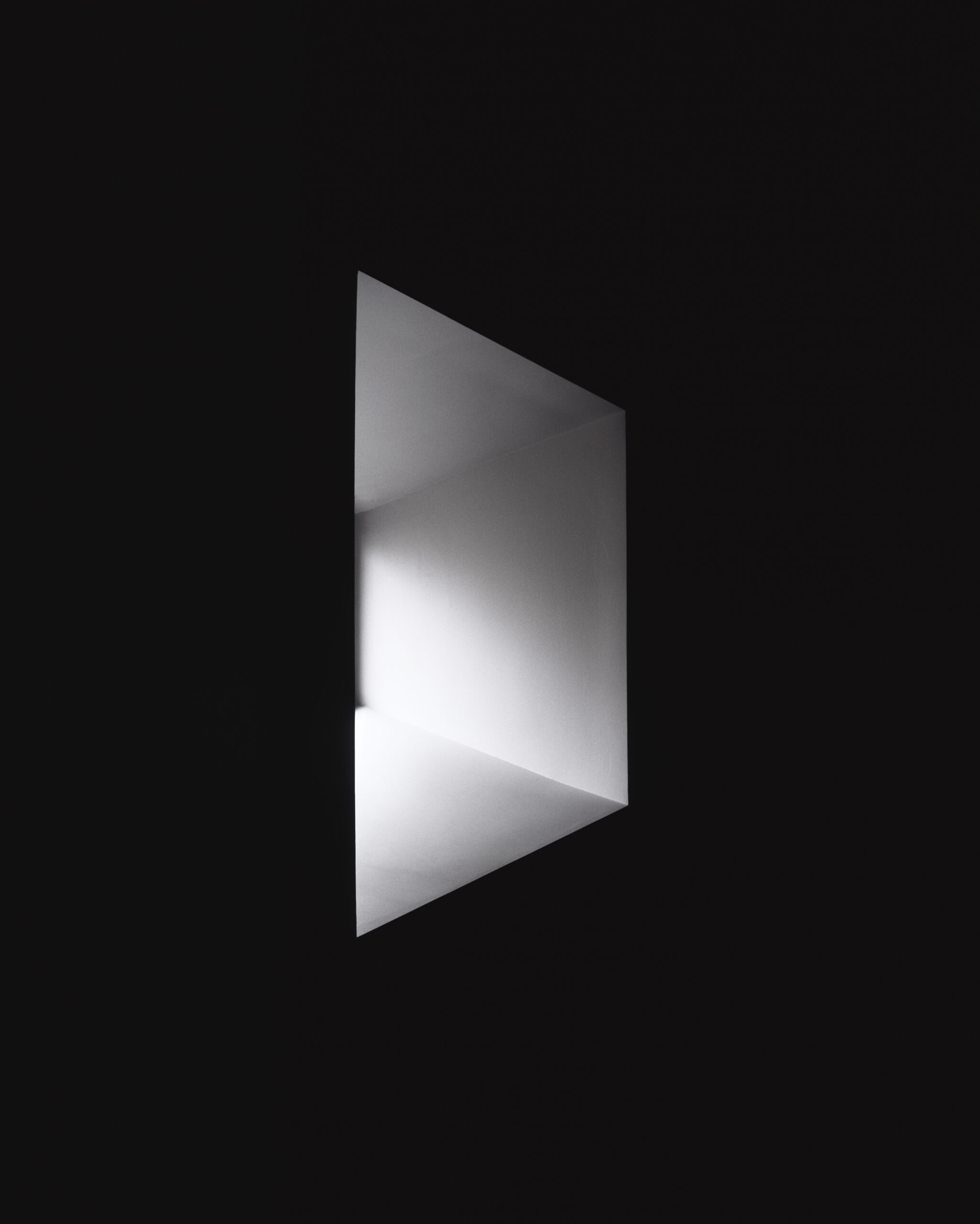 As part of the Autoritratto exhibition by Luisa Lambri, a contrete deep-set window is half a black room and light is coming through the window