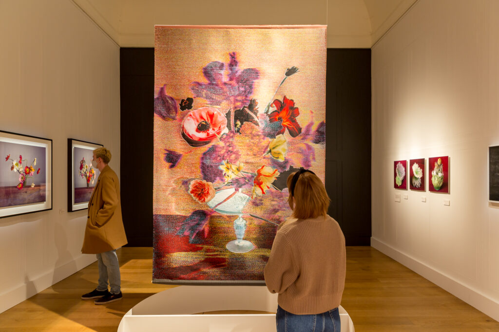 A woman looks up at a tapestry of flowers at the Dulwich Picture Gallery in London.