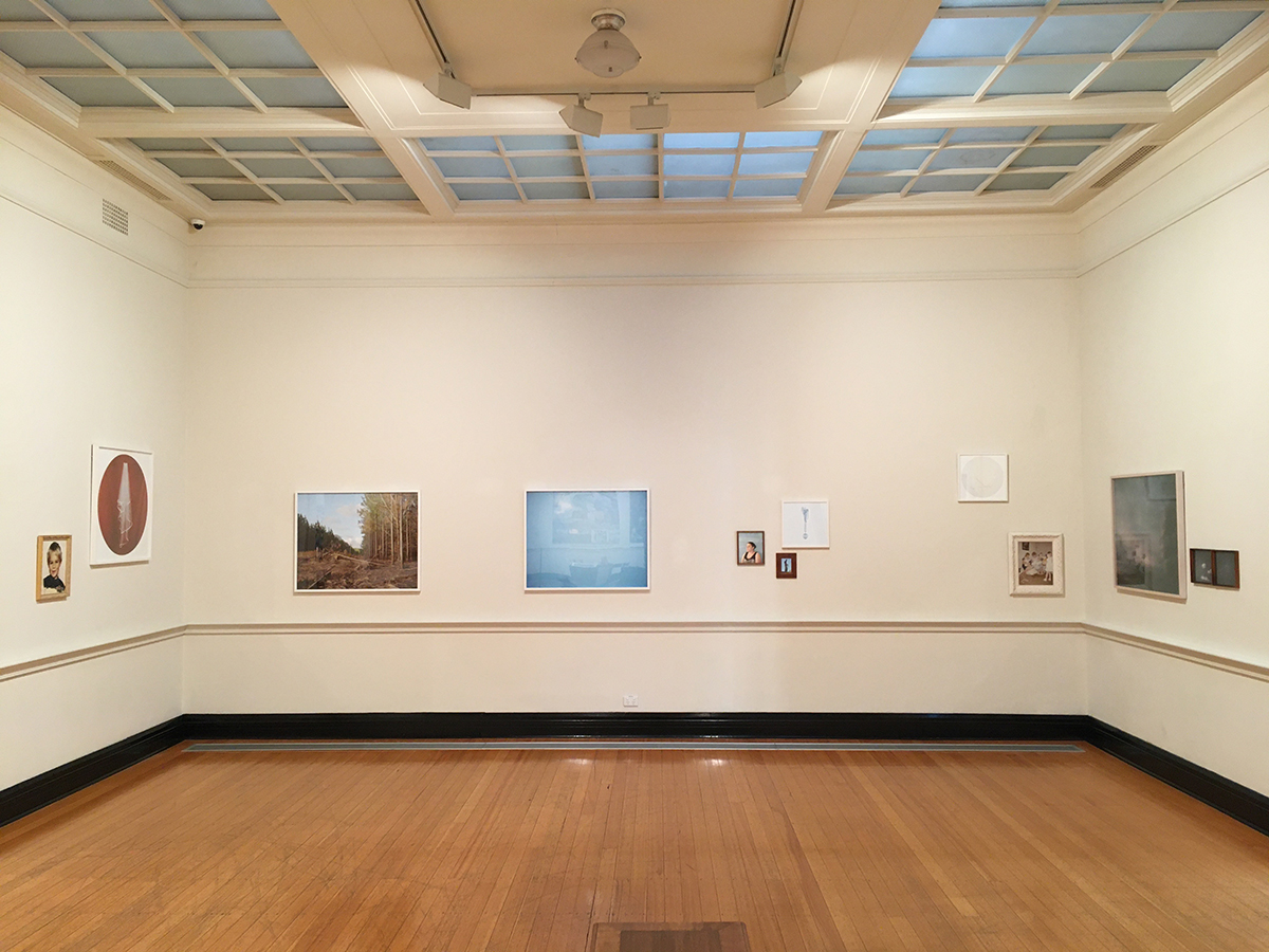Installation images of Cloudy: A Few Isolated Showers. A light wooden floor, beige walls with scattered artworks along the centra of the image. Glass windows are seen in the ceiling.