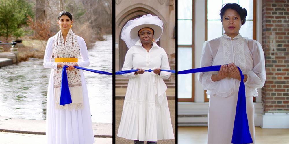 Three women wearing white dresses hold a blue sash